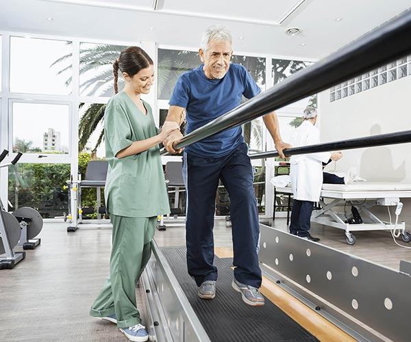 woman assisting a man walking with a balance beam